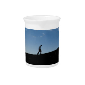 Hombre en silueta de la montaña jarras de beber