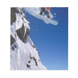 Hombre en una snowboard que salta de una cornisa e libretas para notas