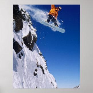 Hombre en una snowboard que salta de una cornisa e impresiones