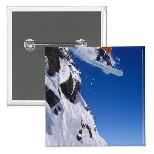 Hombre en una snowboard que salta de una cornisa e pin