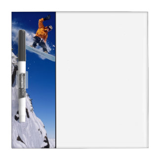 Hombre en una snowboard que salta de una cornisa e pizarras