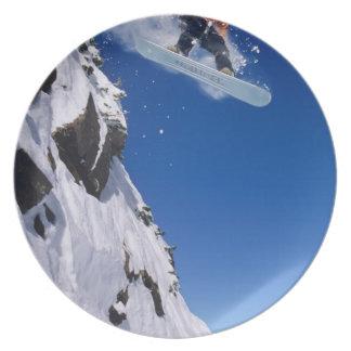Hombre en una snowboard que salta de una cornisa e plato de comida