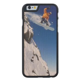 Hombre en una snowboard que salta de una cornisa