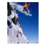 Hombre en una snowboard que salta de una cornisa postal