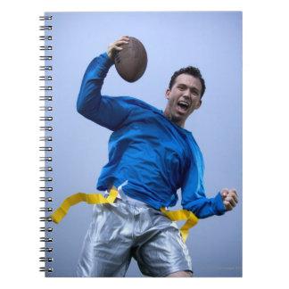 Hombre hispánico que lanza un fútbol libro de apuntes con espiral