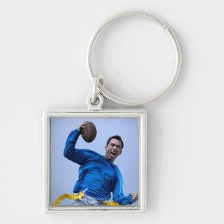 Hombre hispánico que lanza un fútbol llaveros