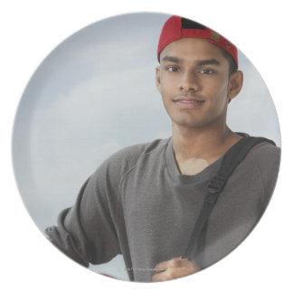 hombre joven con el casquillo rojo que sostiene la plato para fiesta