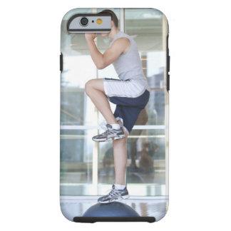hombre joven que hace ejercicios elevadores en un funda resistente iPhone 6