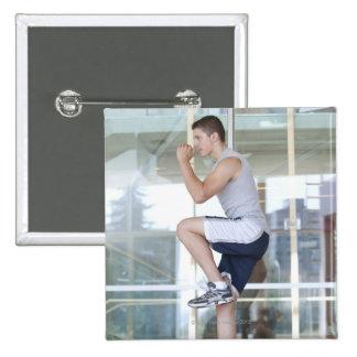 hombre joven que hace ejercicios elevadores en un pin cuadrado