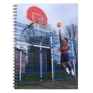 Hombre joven que juega a baloncesto al aire libre libreta