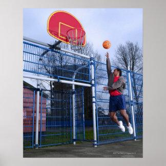 Hombre joven que juega a baloncesto al aire libre póster