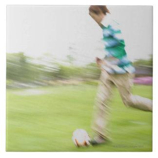 Hombre joven que juega a fútbol azulejo cuadrado grande