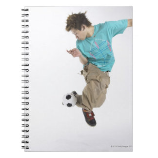 Hombre joven que juega a fútbol libro de apuntes con espiral
