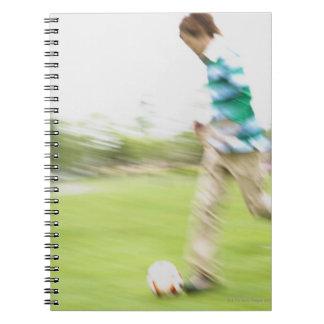 Hombre joven que juega a fútbol cuaderno