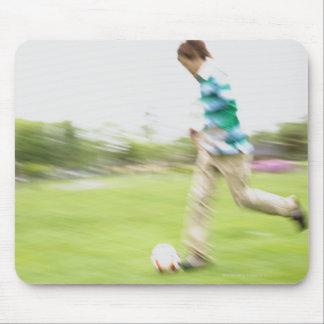 Hombre joven que juega a fútbol alfombrilla de ratones