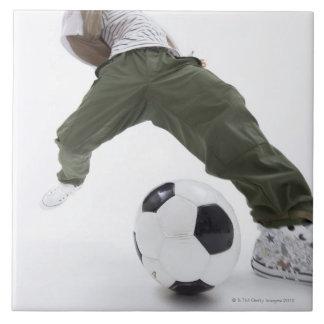 Hombre joven que juega al fútbol 2 azulejo cuadrado grande
