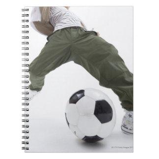 Hombre joven que juega al fútbol 2 cuadernos