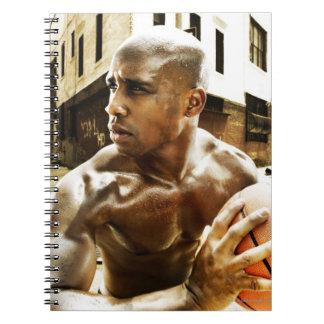 Hombre joven que lleva a cabo baloncesto cuaderno