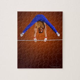 Hombre joven que practica en la barra horizontal puzzles con fotos