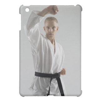 Hombre joven que realiza postura del karate en bla