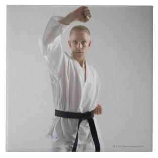 Hombre joven que realiza postura del karate en bla azulejo cuadrado grande