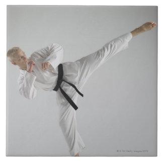 Hombre joven que realiza retroceso del karate en b azulejo cuadrado grande