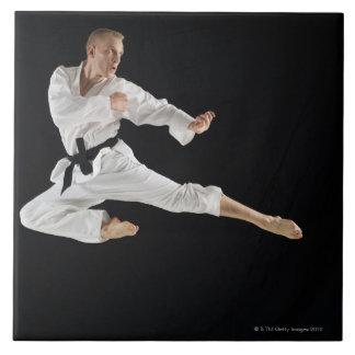 Hombre joven que realiza retroceso del karate en n azulejo cuadrado grande