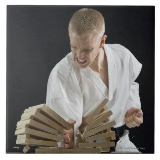 Hombre joven que rompe a tableros con tajada del k azulejo cuadrado grande