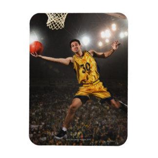 Hombre joven que salta y que lleva a cabo balonces rectangle magnet