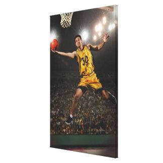 Hombre joven que salta y que lleva a cabo balonces lona envuelta para galerias