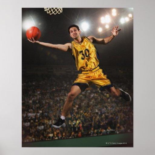 Hombre joven que salta y que lleva a cabo balonces posters