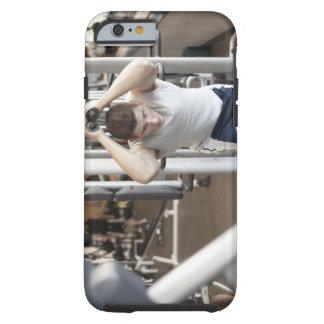 Hombre joven que se resuelve el tríceps en un funda resistente iPhone 6