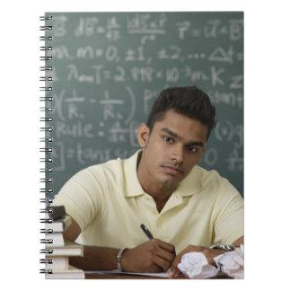 hombre joven que se sienta en su escritorio, escri libro de apuntes