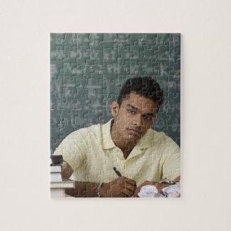 hombre joven que se sienta en su escritorio, escri puzzle con fotos