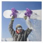Hombre joven que sostiene su snowboard sobre su ca azulejo cuadrado grande