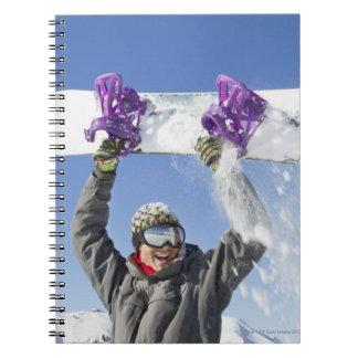 Hombre joven que sostiene su snowboard sobre su ca libro de apuntes