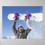 Hombre joven que sostiene su snowboard sobre su ca póster