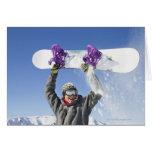 Hombre joven que sostiene su snowboard sobre su ca tarjeta de felicitación