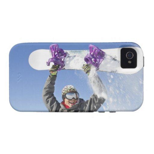 Hombre joven que sostiene su snowboard sobre su Case-Mate iPhone 4 fundas
