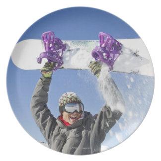 Hombre joven que sostiene su snowboard sobre su plato para fiesta