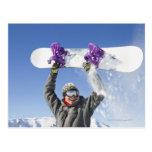 Hombre joven que sostiene su snowboard sobre su tarjetas postales
