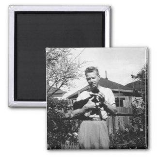 Hombre joven que sostiene un gato imán cuadrado