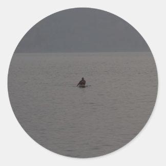 Hombre kayaking en Loch Ness en Escocia Etiqueta Redonda