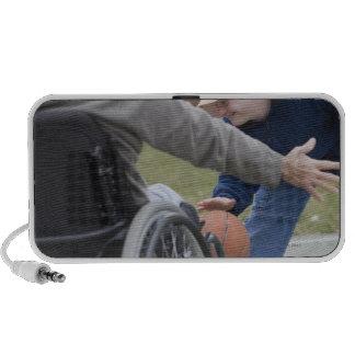 Hombre lisiado que juega a baloncesto con su hijo laptop altavoz