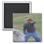 Hombre lisiado que juega a béisbol con su hijo imán de nevera