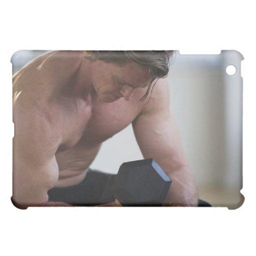 Hombre muscular que levanta el peso libre