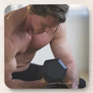 Hombre muscular que levanta el peso libre posavasos de bebidas