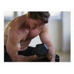 Hombre muscular que levanta el peso libre postal