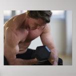 Hombre muscular que levanta el peso libre póster