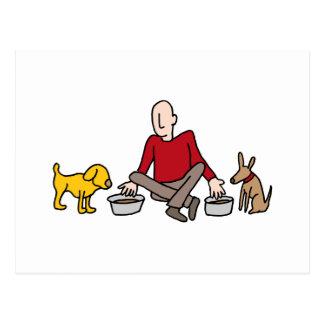 Hombre que alimenta sus dos perros postales